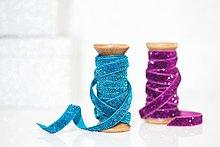 Holzrollen mit funkelndem blauen und violetten Band