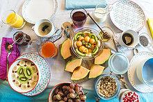 Gedeckter Frühstückstisch mit Müsli und Früchten