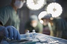Chirurg greift nach Instrument auf Tablett-Operationssaal