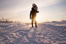 Rückansicht eines Mannes mit Schneeschuhen auf den Schultern in verschneiter Landschaft, Ural, Russland
