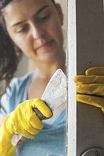 Junge Frau renoviert altes Fenster