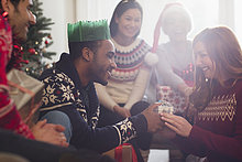 Freunde sehen zu, wie ihr Freund der Freundin ein Weihnachtsgeschenk macht.