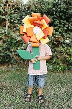 Junge hält hausgemachte Pappblume vor sein Gesicht