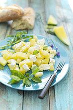 Melonensalat, gelbe Wassermelone, Feta, Minze und Rucola auf dem Teller