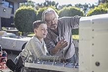 Senior Mann, der dem Jungen den Mechanismus eines Autos erklärt.