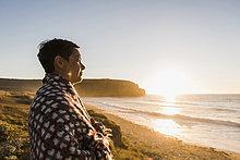 Frankreich, Bretagne, Halbinsel Crozon, Frau an der Küste bei Sonnenuntergang