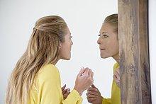 Schöne Frau beim Schminken im Spiegel