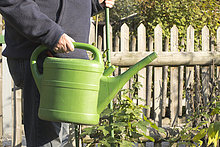 Midsection of senior man holding watering can in garden