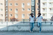 Identische männliche Hipster Zwillinge chatten auf Wohnung Dachterrasse