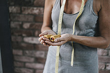 Frau mit Maßband, die Baumwollrollen hält