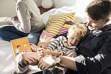 Hochwinkelansicht von Vater und Sohn mit Bilderbuch zum Genießen zu Hause im Bett