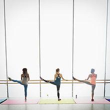 Frauen beim Stretchen der Beine an der Stange im Fitnessstudio der Gymnastikklasse
