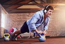Entschlossener junger Mann mit Kopfhörer, der Liegestütze mit Kettlebell macht.