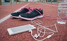 Sportschuhe, Smartphone mit Ohrstöpseln und Wasserflasche auf Tartanbahn