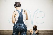 Rückansicht des kleinen Jungen, der seine Mutter beim Malen der Wand beobachtet.