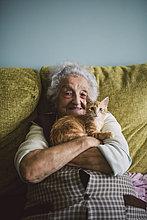 Porträt einer glücklichen Seniorin, die mit ihrer Katze auf der Couch kuschelt.