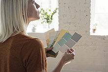Junge Frau im Loft denkt über Farbmuster nach