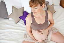 Schwangere Frau sitzt auf dem Bett