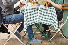 Niedriger Abschnitt des Paares am Bürgersteig-Café-Tisch