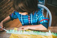 Junge, der Kleber auf Krepppapier aufträgt, um Pinata herzustellen.