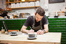 Junge männliche Cafe-Besitzer tun Papierkram am Tisch