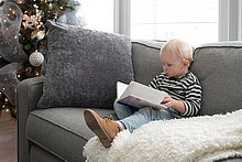 Junge sitzt auf dem Sofa und schaut sich das Buch an.