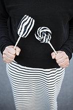 Frau mit schwarz-weißem Rock mit Lakritz-Lolly-Pops