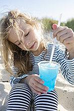 Mädchen am Strand Rühren blau gefrorenes Getränk mit einem Strohhalm