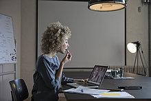 Frau im Büro beim Schminken mit Laptop-Monitor als Spiegel