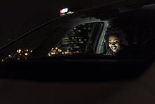 Lächelnde junge Frau sitzt nachts in einem Auto mit Tablette