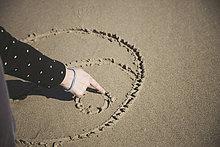 Frau kratzt Yin Yang Symbol im Sand eines Strandes, Nahaufnahme