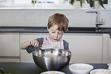 Kleiner Junge hilft bei der Zubereitung des Essens in der Küche