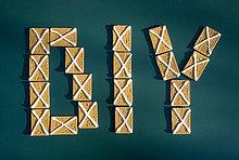 Buchstaben DIY aus Keksen mit Zuckerguss auf grünem Grund