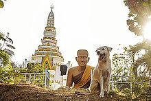 Thailand, Phuket, Blick zum Nai Harn Tempel mit Buddhastatue und Hund im Vordergrund