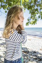 Porträt eines blonden Mädchens, das auf einer Schaukel am Strand steht