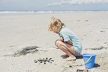 Frankreich, Bretagne, Finistere, Pointe de la Torche, Junge spielt mit Muscheln am Strand