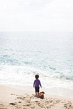 Rückansicht des kleinen Jungen, der neben seinem Hund am Strand steht und auf das Meer schaut.