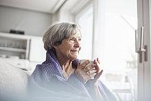 Porträt einer fröhlichen Seniorin auf der Couch zu Hause bei einer Tasse Kaffee