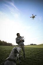 Mann auf einer Wiese fliegt Drohne, während sein Hund zusieht.