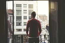 Mann auf einem Balkon in der Stadt bei Sonnenuntergang