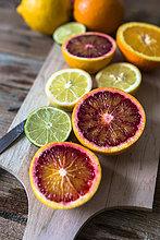 Geschnittene Zitrone, Orangen und Limette auf Holzplatte