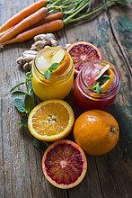 Zwei Gläser mit verschiedenen Orangensäften, Orangen, Karotten, Minzeblättern und Ingwer.