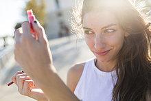 Junge Frau mit Taschenspiegel zur Kontrolle ihres Make-ups