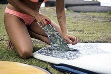 Frau bereitet Surfbrett auf der Wiese vor