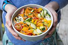 Hände halten Schüssel Reissalat mit gemischtem Gemüse
