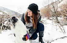 Junge Frau spielt mit ihrem Hund im Schnee