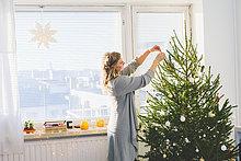 Finnland, Helsinki, Frau schmückt Weihnachtsbaum