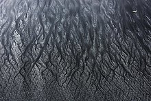 Weißer und schwarzer Sand, ablaufendes Wasser bei Ebbe, Strukturen im Sand, Talisker Bay, Isle of Skye, Schottland, Großbritannien, Europa