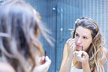 Reflexion einer jungen Frau im Spiegel beim Schminken
