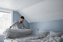 Glücklicher Mann bereitet das Bett zu Hause vor
